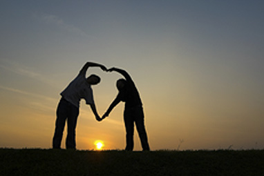 couple create love heart silhouette against setting sun