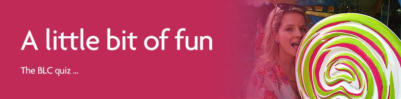 a little bit of fun, attractive woman licks enormous lolly pop at fun fair