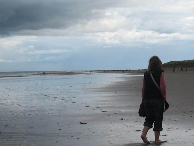 single woman walks on beach at beaumaris being dumped at Christmas