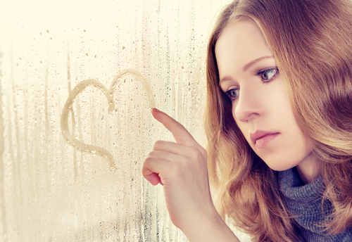 sad enamoured girl with Valentine blues draws a heart on the window in the rain.
